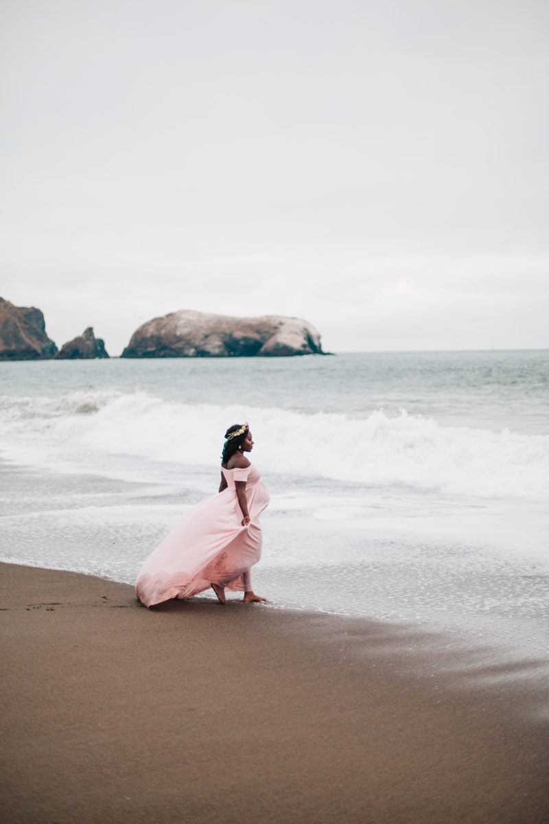 Maternity Photographer, woman in blush dress standing at the ocean