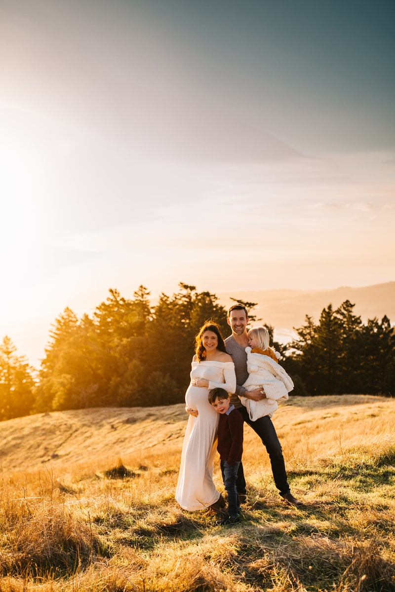 Maternity Photographer, family of 4 standing on hillside