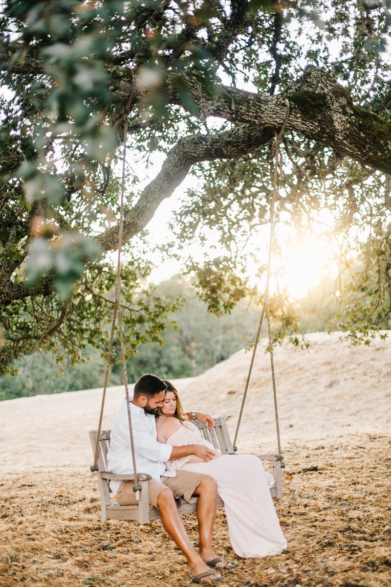 Maternity Photographer, coupld sitting on a swing together