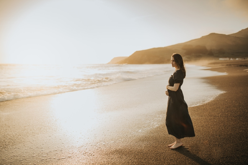 Maternity Photographer, woman standing on the beach