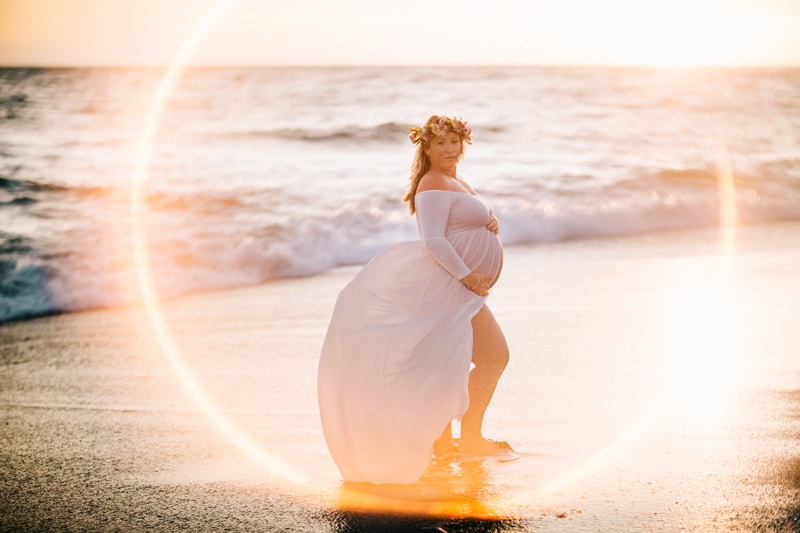 Maternity Photographer, woman in white standing at the beach with sunset behind her
