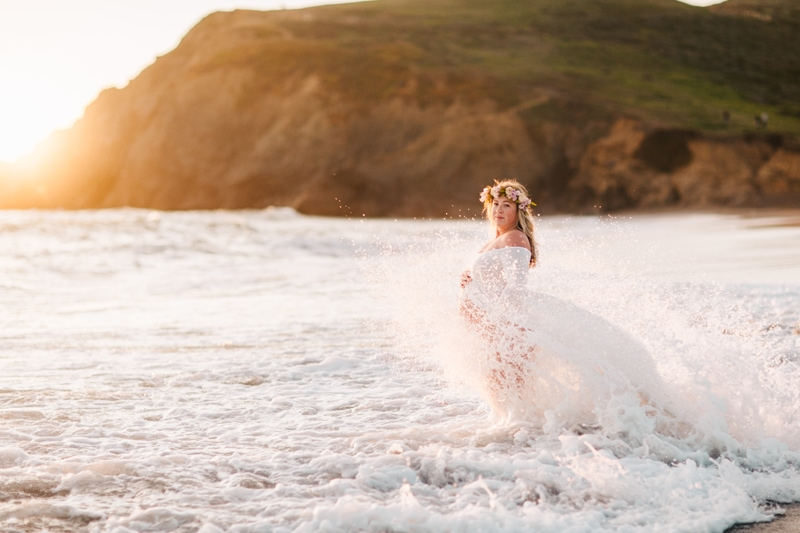 Maternity Photographer, mother standing in a splashing wave at beach