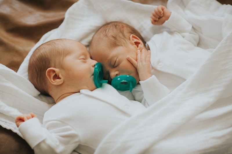 Newborn Photographer, twins with pacifiers sleeping next to each other