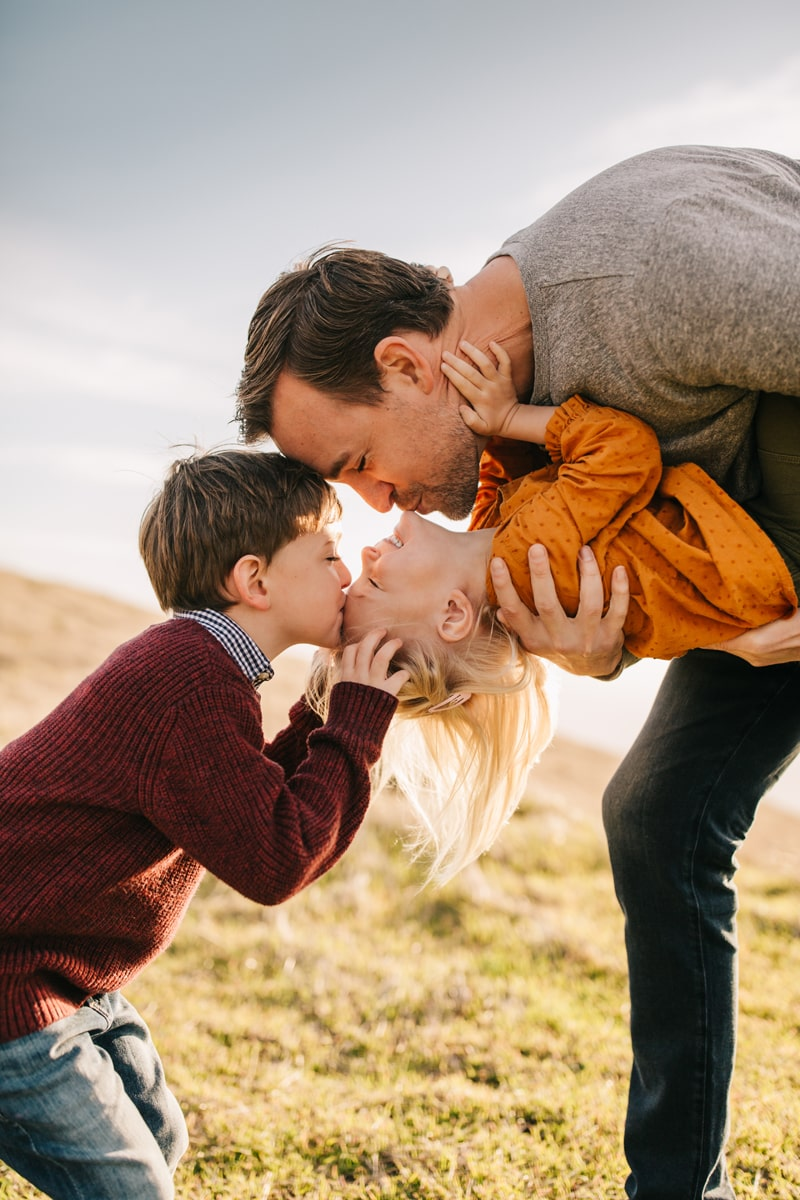 Family Photographer, father leaning down to let son kiss sister on her forhead