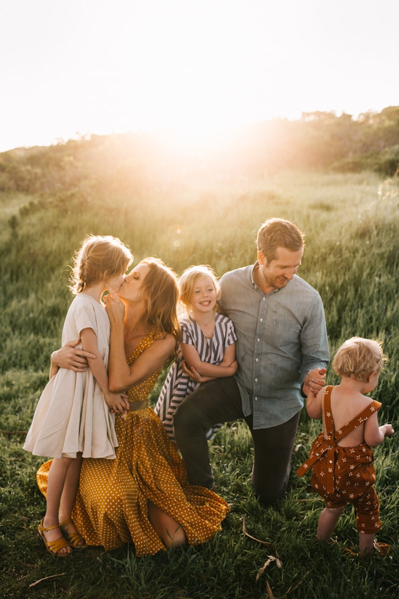 Family Photographer, family of 5 smiling and playing together with sunset behind them