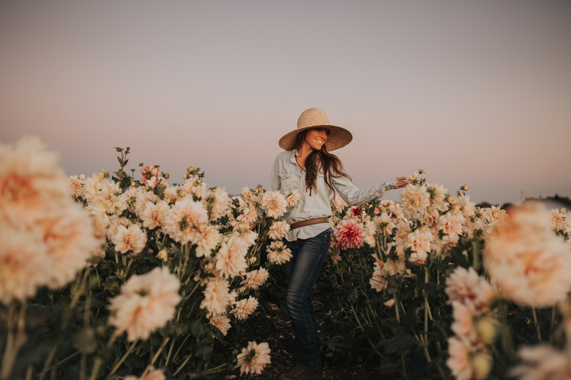 Family Photographer, woman in wide-brim hat standing in a flower field