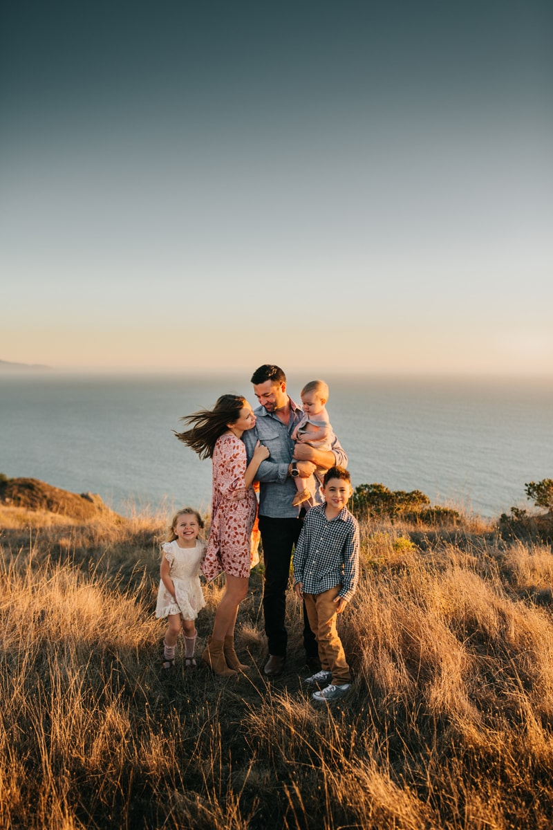 Family Photographer, family of 5 standing together on a hillside