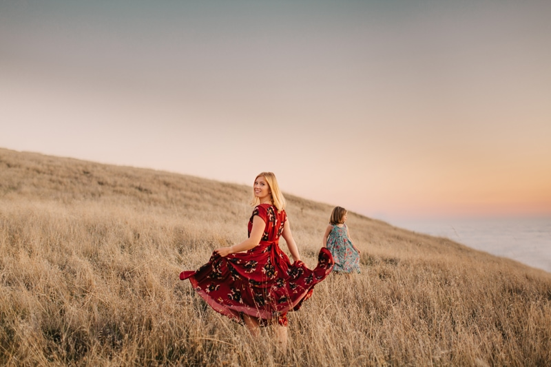 Family Photographer, mother and daughter twirling their dresses in a field