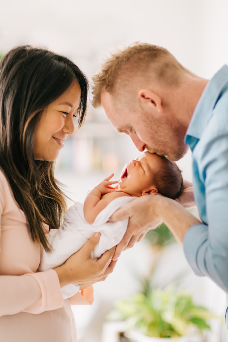 Newborn Photographer, mother holding baby while dad kisses its forehead