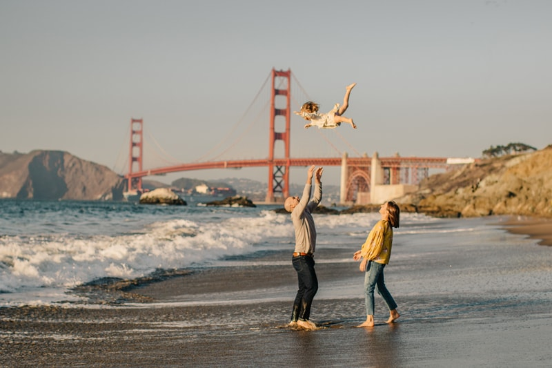 Family Photographer, dad throwing little girl into the air to catch her
