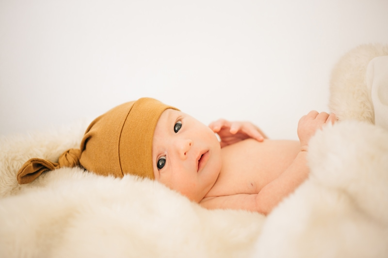 Newborn Photographer, baby in mustard colored beanie looking to its side