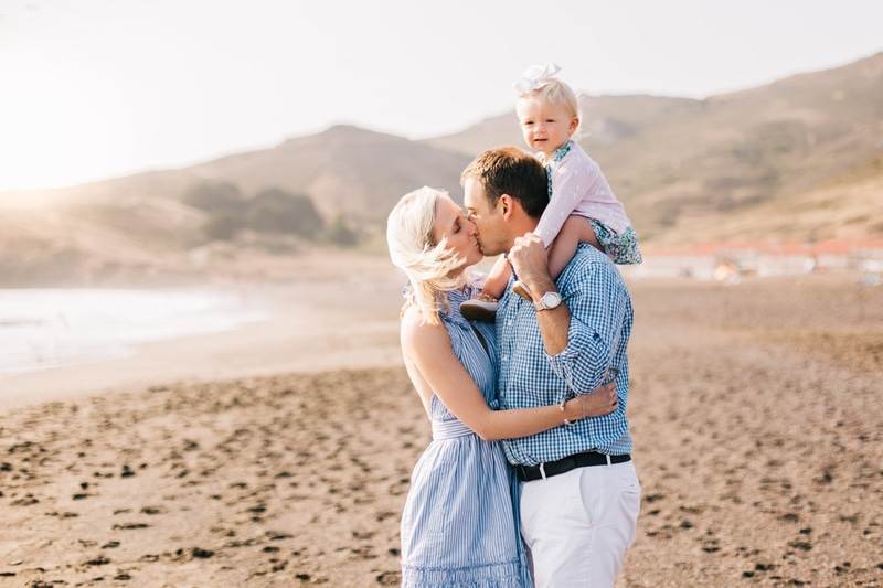 Family Photographer, mother and father kissing at the beach with baby on dad's shoulders