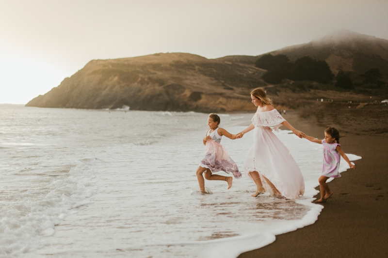 Family Photographer, mother walking into the ocean with her daughters