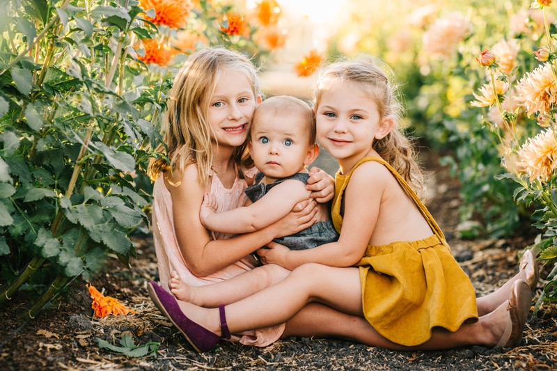 Family Photographer, three siblings sitting together in a flower field