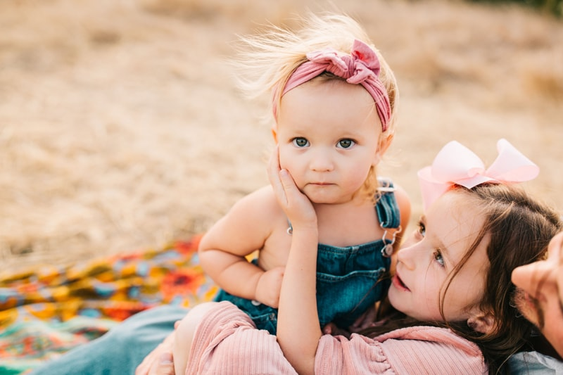 Family Photographer, little girl sitting on dads lap with older sister