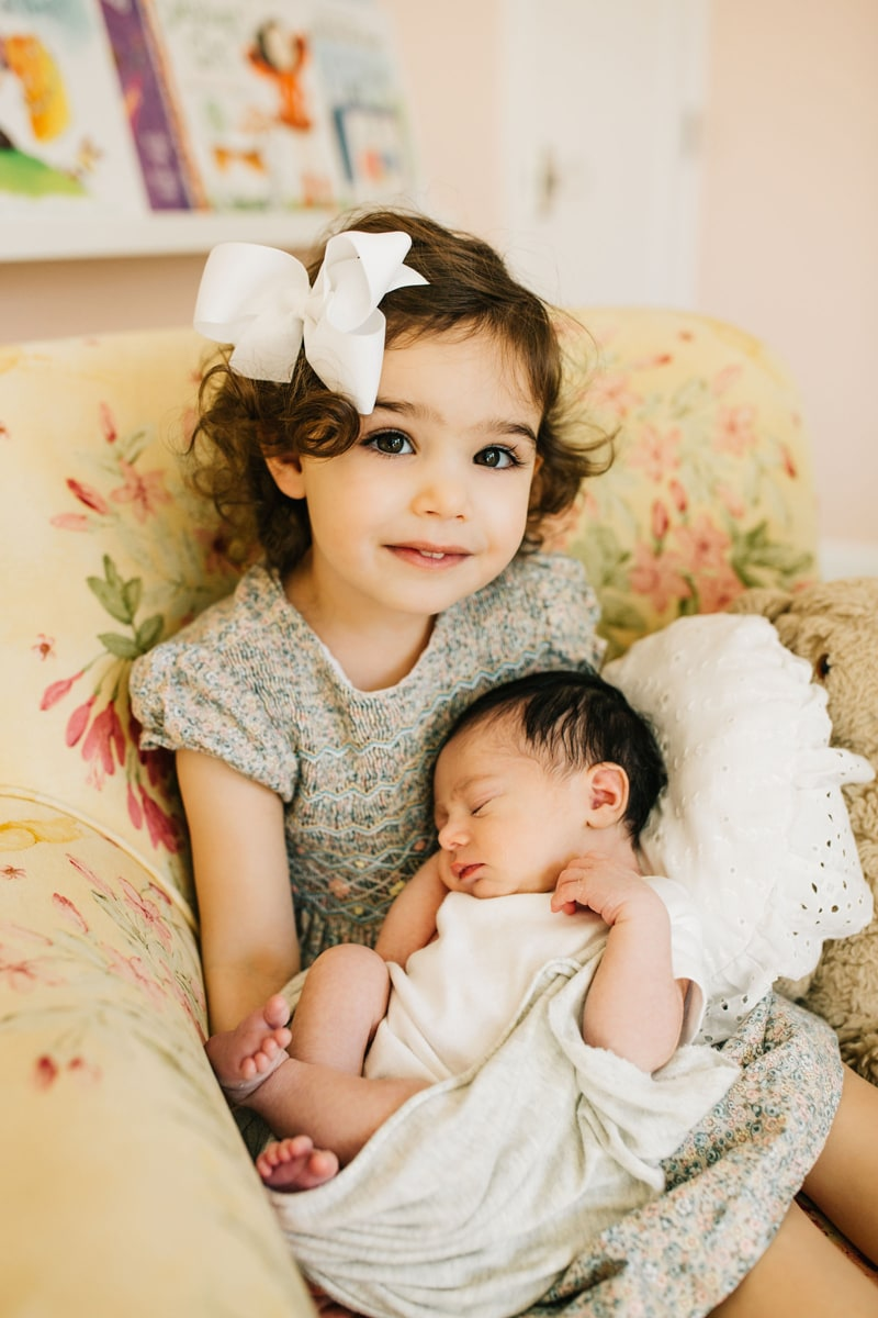 Newborn Photographer, newborn baby asleep in little sister's arms