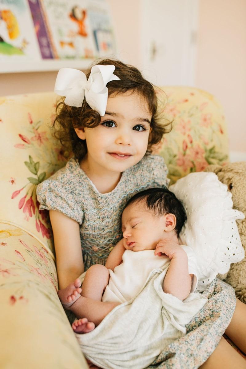 Newborn Photographer, newborn baby asleep in little sister's arms