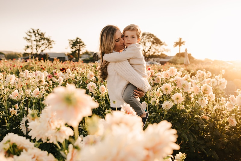 Family Photographer, mother and son standing in a flower field