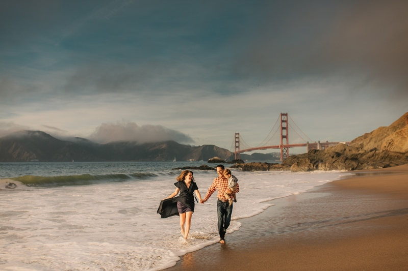 Family Photographer, family of three walking on the beach with the Golden Gate Bridge behind them