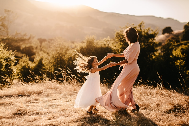 Family Photographer, mother and daughter dancing around on a hill side