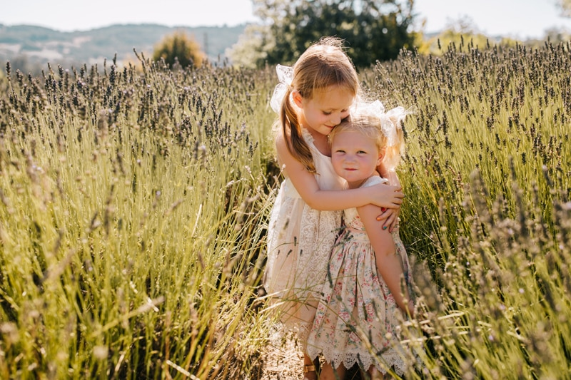 Family Photographer, sister hugging little sister in a field of wildflowers