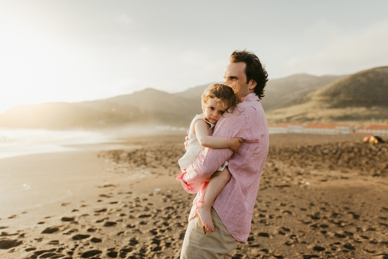 Family Photographer, father holding daughter at the beach