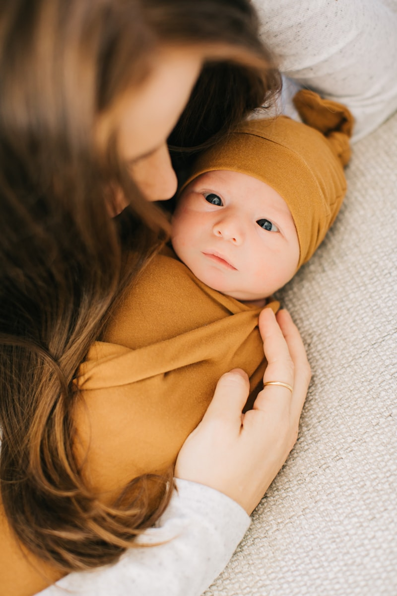 Newborn Photographer, baby wrapped in mustard blanket and beanie